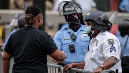 cop and protestor shaking hands