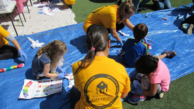 """""""Volunteers playing with children"""" Photo courtesy of Holy Family Day Home"""